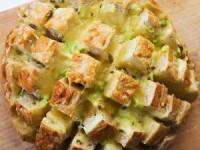 Ингредиенты: 1 деревенский хлеб 340 г тертого сыра 1/4 чашки (меньше или больше по вкусу) нарезанного маринованного перца чили 1/4 чашки нарезанного зеленого лука, зелень в том числе 4 ст.л. размягченного сливочное масло Приготовление: 1. Разогреть духовку до 180С. Нарежьте весь хлеб почти до донышка в клеточку. 2. Натереть сыр в большую миску. Добавить зеленый лук с перцем чили. Полить растопленным сливочным маслом, тщательно перемешать руками. 3 Положите хлеб на большой лист фольги (достаточно большой, чтобы обернуть хлеб). Наполните каждую трещину сырной смесью. Завернуть в фольгу. 4. Поставить хлеб в духовку на 15 минут. Затем раскрыть фольгу от хлеба и поставить еще на 10 минут, пока все сыр не расплавится.
