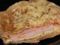 Ингредиенты: На 1 порцию: армянский лаваш (тонкий)- 0,5-1 шт, кружок помидора, кружок ветчины, яйцо - 1 шт, зелень сыр твердый - 20 г, сливочное или растительное масло для жарки, соль, перец Приготовление: Помидор вымыть и порезать на кружочки. Сыр натереть на терке. Зелень вымыть, обсушить и порубить. Нарезать ветчину. Лаваш хорошо сбрызнуть холодной водой и положить на разогретую с растительным или сливочным маслом сковороду так, чтобы края свисали за бортики сковороды (зажареной стороной вверх). Если лист лаваша большой - разрежьте его пополам. В середину листа лаваша положить кружок помидора . Немного посолить. Сверху на помидор кружок ветчины (у меня - вареная колбаса). Затем разбить сырое яйцо. Посолить, поперчить. Сверху все посыпать тертым сыром и рубленой зеленью (сегодня у меня зелени не нашлось). Подвернуть края лаваша к центру и жарить до румяной корочки (можно сделать сильно или средне зажаренную корочку по желанию). Аккуратно перевернуть на другую сторону,посыпать сверху тертым сыром и жарить еще несколько минут, до румяной корочки. Подавать закуску горячей.